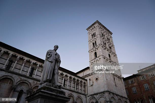 Side view of San Michele in Foro with bell tower in Lucca with a statue of Francesco Burlamacchi holding sword