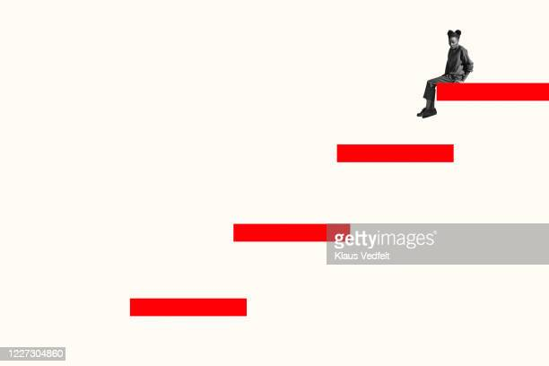 side view of scared woman sitting on top red step - degraus imagens e fotografias de stock