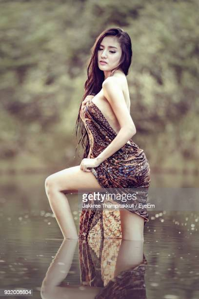 side view of seductive woman standing in lake at forest - adults only photos stock photos and pictures