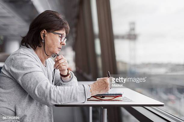 Side view of senior businesswoman using hands-free device by window in office