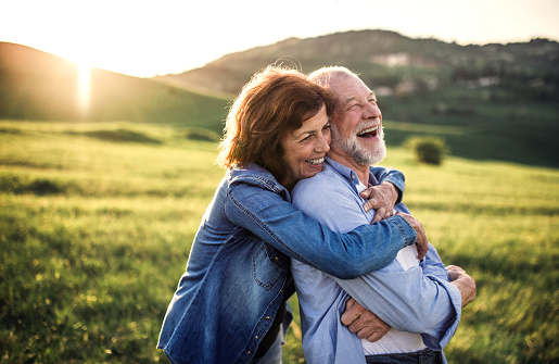 Side view of senior couple hugging outside in spring nature at sunset. 1027141710