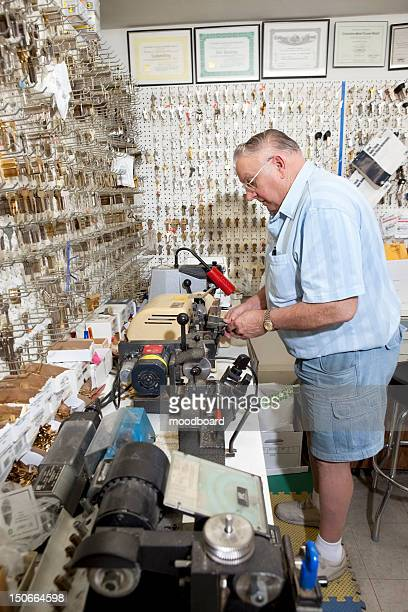Side view of senior locksmith working in store