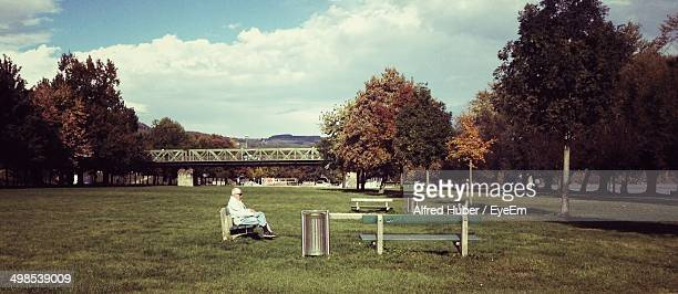 side view of senior man sitting on park bench - one senior man only stock pictures, royalty-free photos & images