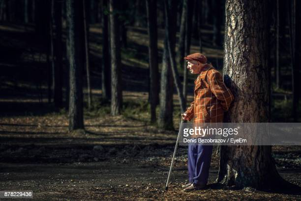 Side View Of Senior Man Standing By Tree Trunk