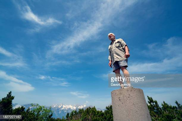 side view of  senior man, standing on pillar with the feeling that he is the top of the world - moment of silence stock pictures, royalty-free photos & images