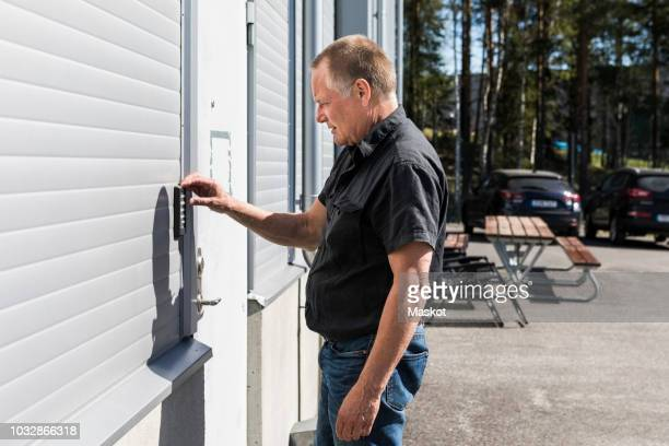 Side view of senior man unlocking door at warehouse entrance