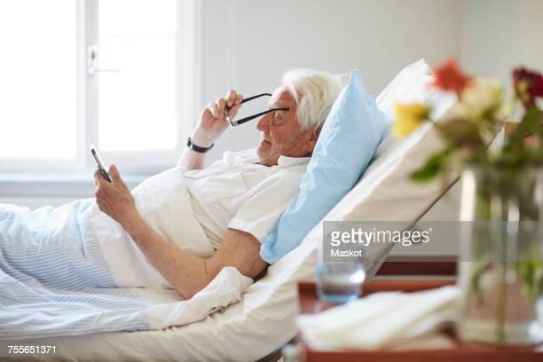 Side view of senior man wearing eyeglasses while using smart phone in hospital ward