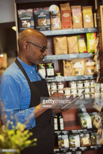Side view of senior owner using digital tablet at store