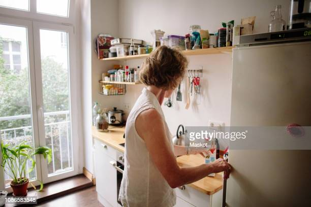 side view of senior woman holding milk carton in kitchen at home - milk carton fotografías e imágenes de stock