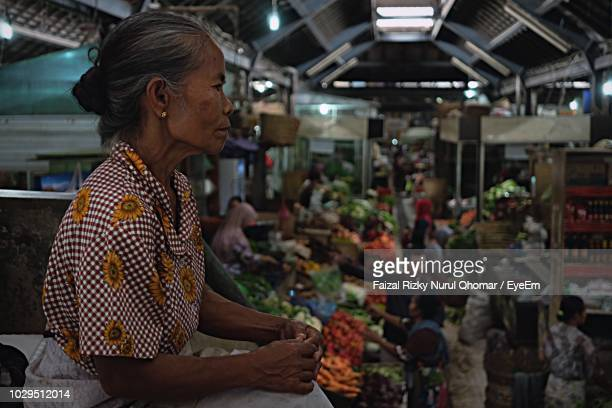 side view of senior woman in market at night - java indonesia fotografías e imágenes de stock