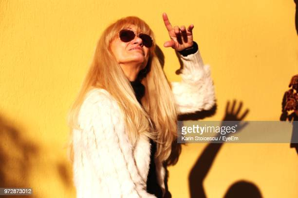 Side View Of Senior Woman Pointing While Standing Against Yellow Wall During Sunset