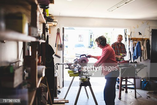 Side view of senior woman using circular saw while man holding drill in background