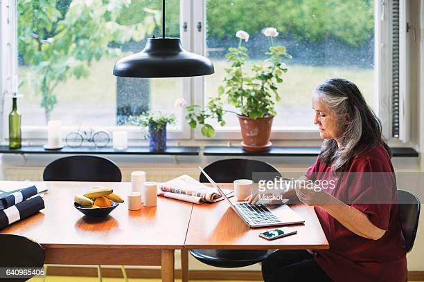 Side view of senior woman using credit card for online shopping at home