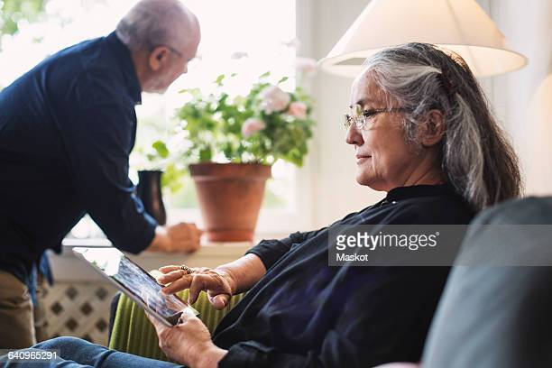 Side view of senior woman using digital tablet while man looking at plant
