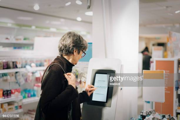 side view of senior woman using kiosk at pharmacy store - kiosk stock pictures, royalty-free photos & images