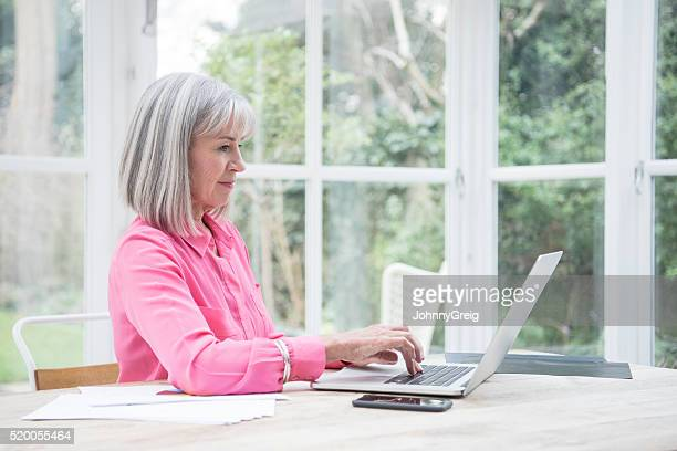 Side view of senior woman using laptop computer