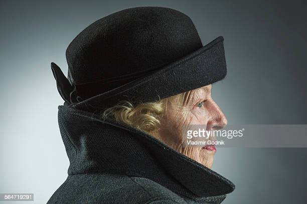 Side view of senior woman wearing hat and jacket against gray background