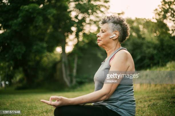 side view of senior woman with in-ear headphones sitting in lotus position at park - buddhism stock pictures, royalty-free photos & images