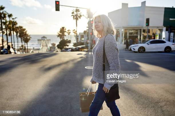 side view of senior woman with shopping bag walking on road in city during sunset - cruzar fotografías e imágenes de stock