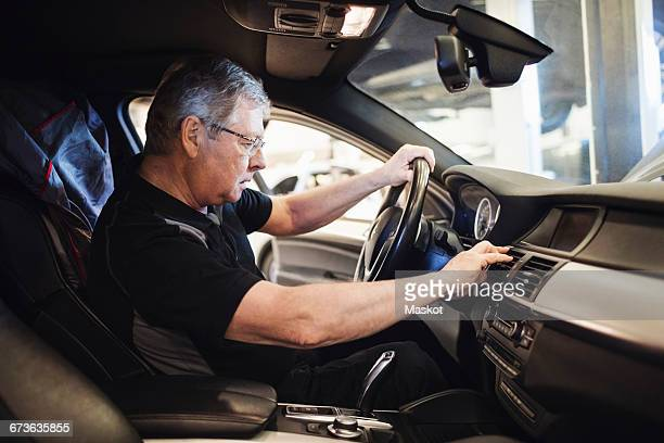 Side view of senior worker examining air conditioner while sitting in car