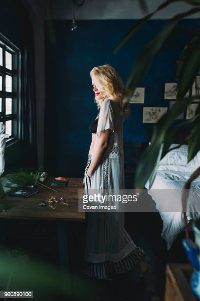 Side view of sensuous woman standing by table in bedroom