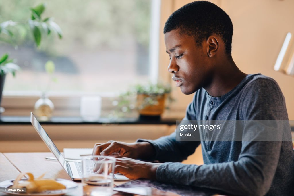 Side view of serious boy using laptop on table while sitting against window at home : Stock Photo