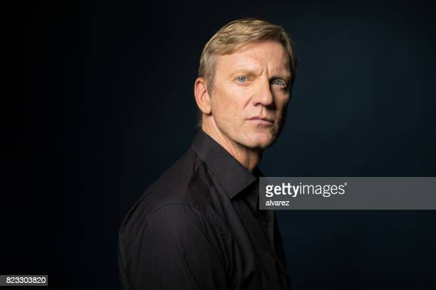 Side View Of Serious Man Against Black Background
