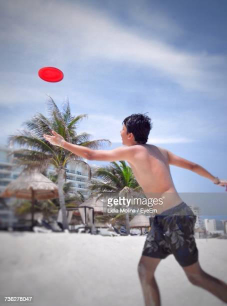Side View Of Shirtless Man Catching Plastic Disc While Running At Beach