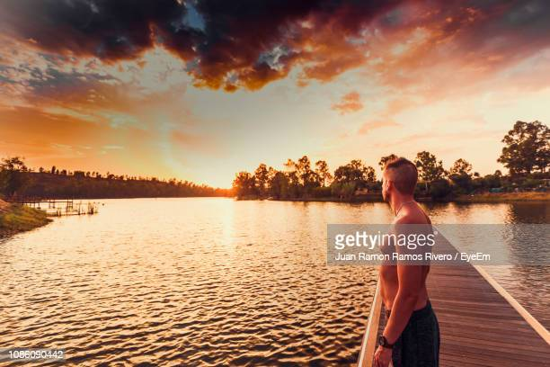 Side View Of Shirtless Man Standing On Pier Over During Sunset