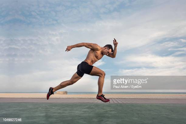 side view of shirtless man taking running stance against sky - aikāne stock pictures, royalty-free photos & images