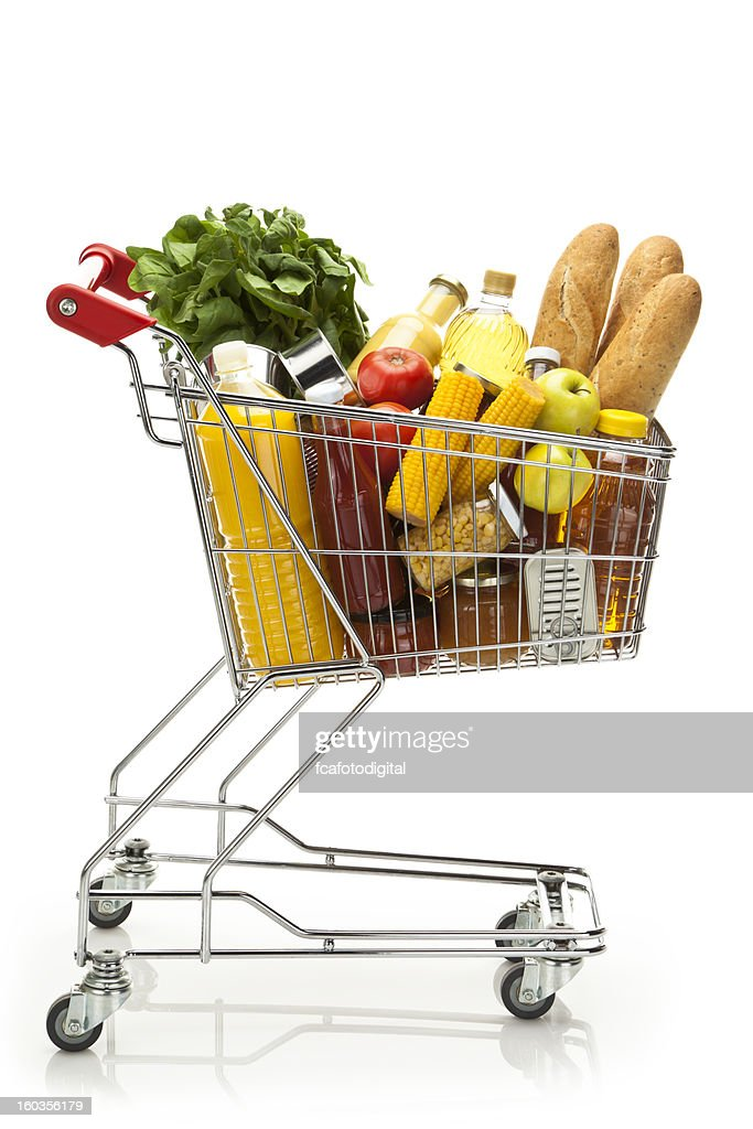 Side view of shopping cart filled with groceries and vegetables : Stock Photo