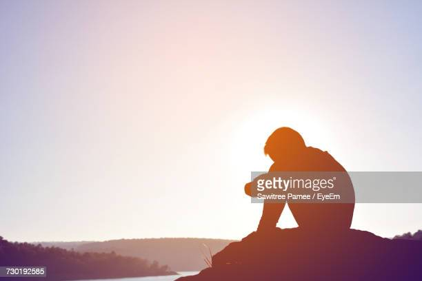 Side View Of Silhouette Boy Sitting Against Sky During Sunset