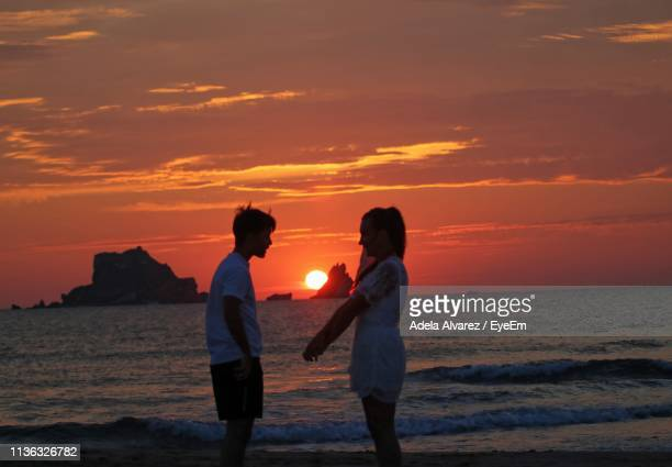 Side View Of Silhouette Couple Standing On Beach Against Cloudy Sky During Sunset
