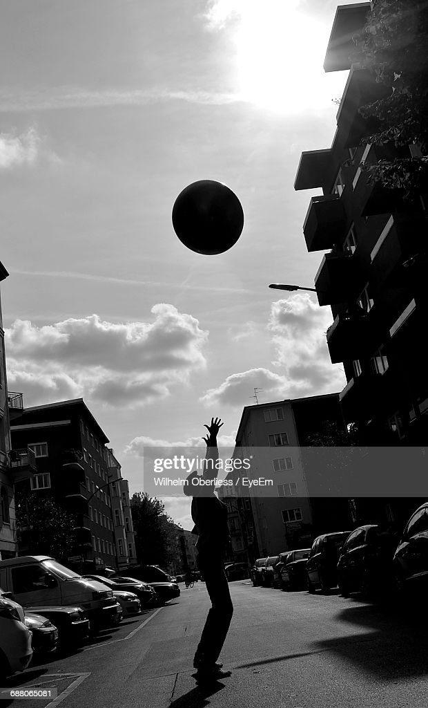 Side View Of Silhouette Man Catching Ball On Street During