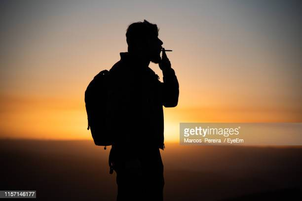 side view of silhouette man smoking cigarette against sky during sunset - 35 39歳 ストックフォトと画像