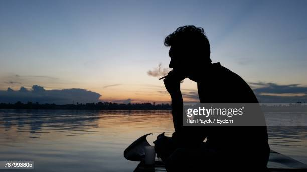 Side View Of Silhouette Man Smoking Cigarette By River During Sunset