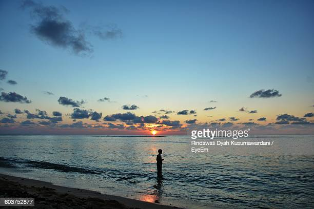 side view of silhouette man standing in sea at sunset - nuku'alofa stock pictures, royalty-free photos & images