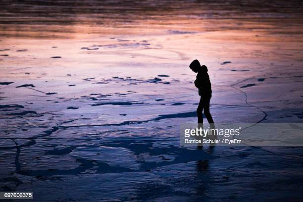 Side View Of Silhouette Person Walking On Frozen Wentzell Lake At Dusk
