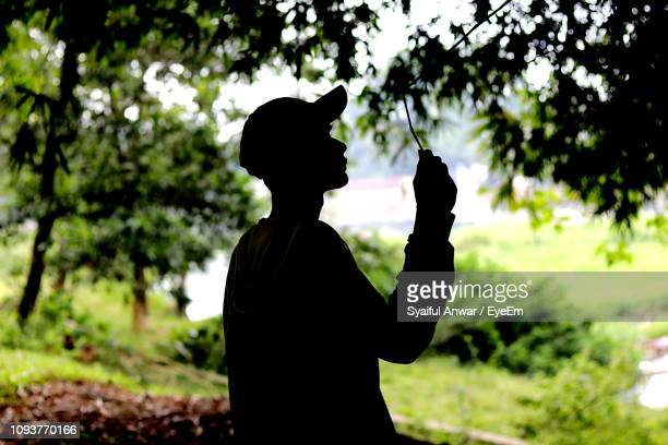 Side View Of Silhouette Teenage Boy Standing By Tree In Park