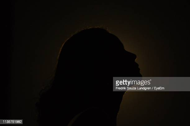 side view of silhouette woman against black background - controluce foto e immagini stock