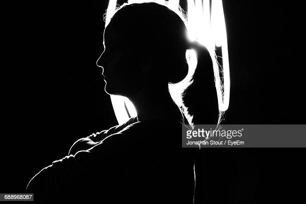Side View Of Silhouette Woman Against Illuminated Lighting Equipment In Darkroom