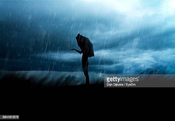 side view of silhouette woman holding umbrella against cloudy sky during rainy season at night - 集中豪雨 ストックフォトと画像