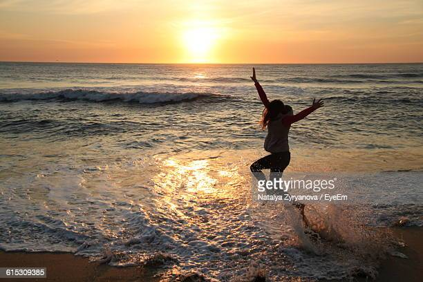 Side View Of Silhouette Woman Jumping On Beach At Sunset