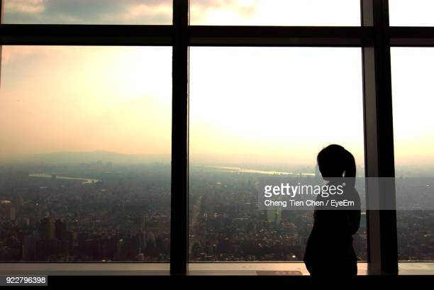 Side View Of Silhouette Woman Looking Through Window At Sunset