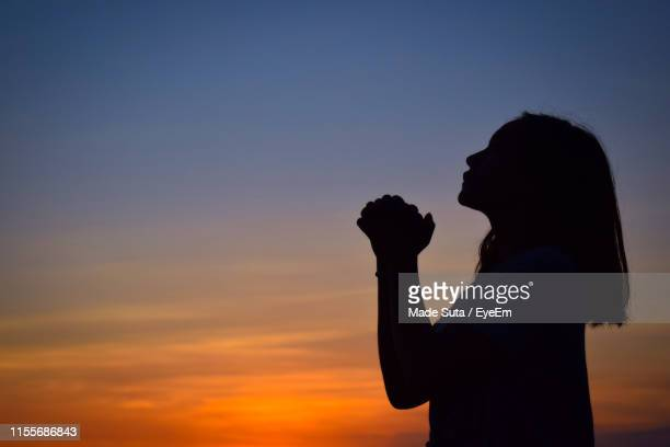 side view of silhouette woman praying while standing against sky during sunset - forgiveness stock pictures, royalty-free photos & images