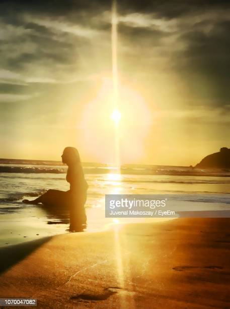 Side View Of Silhouette Woman Sitting At Beach During Sunset