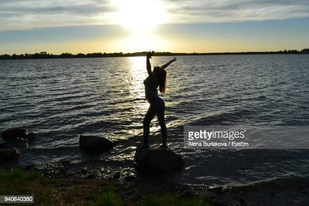 side view of silhouette woman standing on rock at lakeshore during sunset - burlakova stock-fotos und bilder