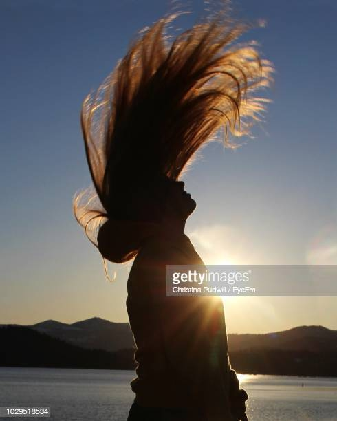 side view of silhouette woman tossing hair against sky during sunset - christina luft stock-fotos und bilder