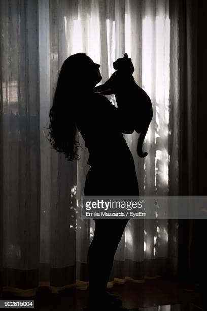 Side View Of Silhouette Woman With Cat At Home