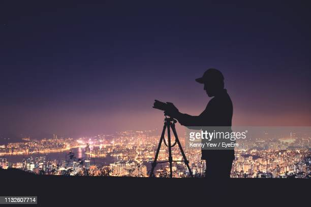 side view of silhouette young man photographing while standing on building terrace against cityscape at night - 三脚 ストックフォトと画像